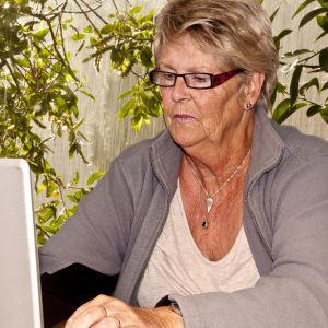 En äldre dam vid en dator.