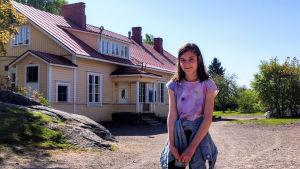 En ung flicka står på en skolgård.