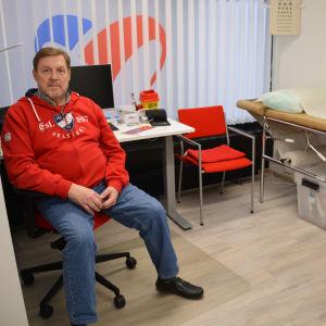 Man i röd tröja på läkarmottagning