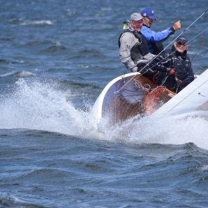 En segelbåt med tre män ombord. Sol och rejäl vind i seglen plus fart på båten.