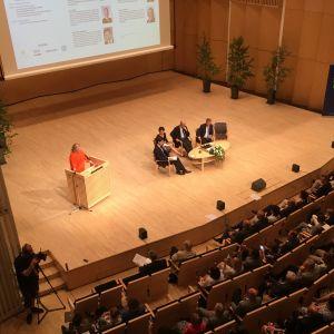 puhuja ja neljä panelistia kokoussalin lavalla