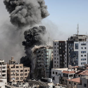Byggnaden i mitten rasar efter att ha träffats av en raket. En rökpelare tornar upp från rasmassorna.