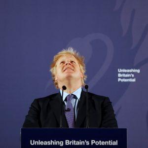 Boris Johnson står framför en blå bakgrund och tittar leende upp i luften.