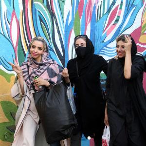 Kolme naista kävelee rinnakkain kadulla.