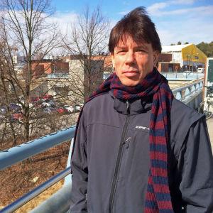 Johan Ekroth står på en bro i solsken, i bakbrunden bilar och hus.