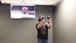 En man med VR-glasögon spelar ett spel där rymdvarelser ska stoppas.