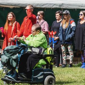 Rykelmä ihmisiä telttaterassin edustalla, etualalla mies sähkökäyttöisessä pyörätuolissa.