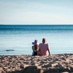 Hattupäinen nainen ja raitapaitainen mies istuvat hiekkarannalla katsomassa merta.