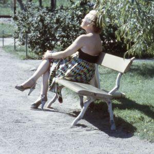 Nainen istuu puistonpenkillä aurinkoa ottaen.