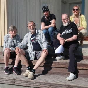 5 glada människor sitter på estraden vid Dalsbruks torg.