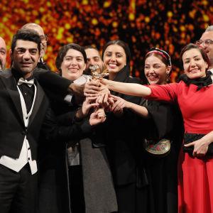 Ett gäng kvinnor och män poserar medan de håller i ett pris som är formad som en guldig björn.