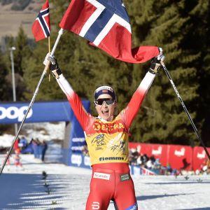 Therese Johaug jublar med den norska flaggan då hon korsar mållinjen.