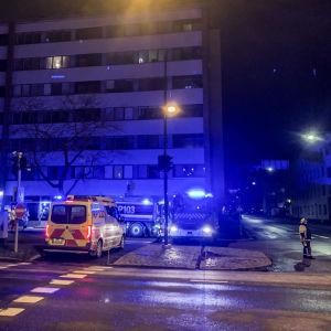 Brandbilar och ambulans med blåljus på, står parkerade vid ett höghus vid en esplanad. Det är mörkt.