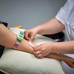 En sjukvårdare tar ett blodprov.