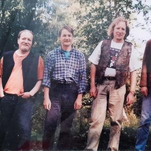 Viisi rennosti pukeutunutta miestä seisoo metsikön edessä rivissä ja katsoo kameraan.