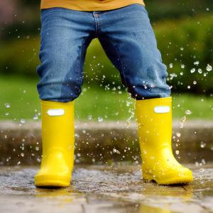 Barn plaskar i vattenpöl