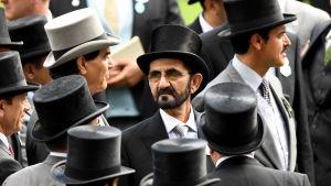 Man i hatt omgiven av andra svartklädda män i hatt.
