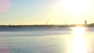 Ett hav och i bakgrunden syns hamnverksamhet.