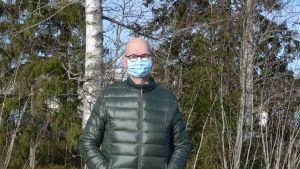 man i grön dunjacka står vid en skogsdunge.