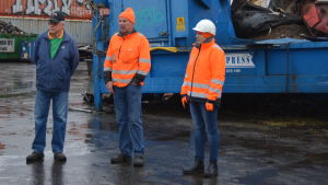 Två män och en kvinna står på en industrigård. I bakgrunden blåa containrar.