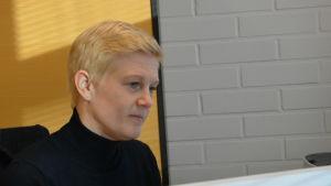 Maria Sainio, en dam med kort, blont hår och svart tröja sitter vid sin dator.
