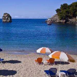Bild på strand med blåvita och orangevita parasoll och solstolar.