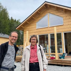 Pekka och Kristiina står framför sin sommarstuga i trä.