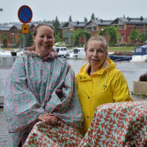 Två kvinnor i regnrockar på promenad med barnvagn.