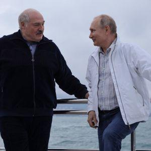 Aleksandr Lukasjenko och Vladimir Putin står på en båt och ler mot varandra.
