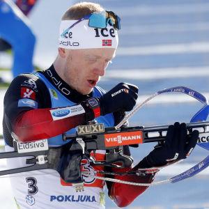 Johannes Thingnes Bø tittar på sitt vapen.
