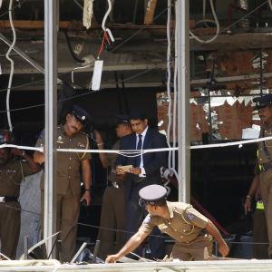 Myndigheter granskar en söndersprängd lokal i hotellet Shangri La i Sri Lanka.