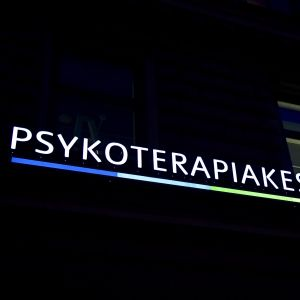 Pstkoterapicentret Vastaamos logo på en mörk husfasad.
