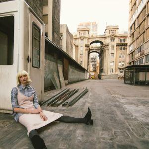 Kvinna sitter och lutar mot en vägg på en tom gata.