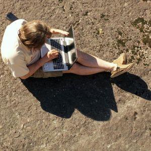 En person sitter med en laptop i famnen på en klippa.