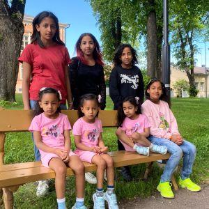 Sju flickor i olika åldrar står uppradade för bild vid en bänk i en park.
