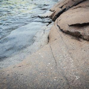 Kallioon hakattu nimet Niko ja Milla ja päivämäärä 17.5.2013