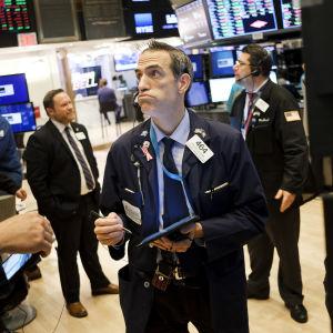 En manlig börsmäklare i kostym och butter min står omringad av andra kostymklädda män med skärmar som visar börskurser omkring.