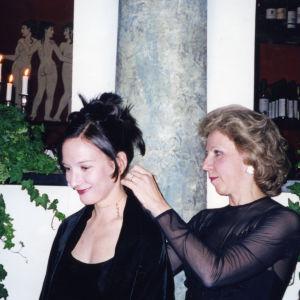 Professori Leena Palotie kiinnittää juuri väiteleelle Iris Hovatalle korua hänen karonkassaan.