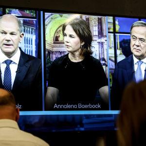 Tre tyska politiker sida vid sida på en tv-skärm. I förgrunden personer som tittar på skärmen.