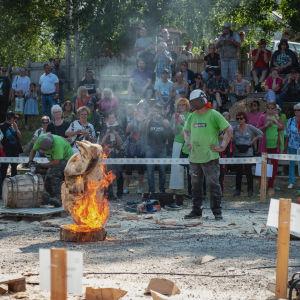 Moottorisahaveistokilpailussa teos palaa, veistäjä viimeistelee tulella, ihmiset katsovat