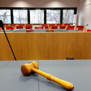 En rättssal, bilden tagen från domarens perspektiv. I förgrunden en domarklubba.