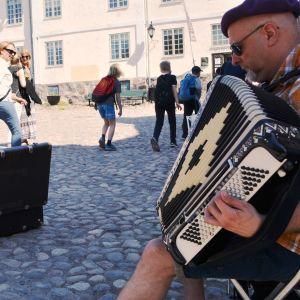 Dragspel och folk som går förbi, Rådhustorget i Borgå Gamla stan.