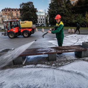 En man tvättar en bänk med högtrycksspruta i Moskva.