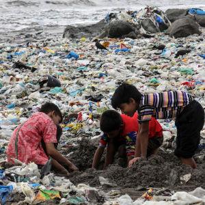 Några barn leker bland skräp o Mumbai, Indien.