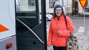 En kvinna i röd jacka håller på att stiga in i en buss på Borgå busstation. Hon tittar in i kameran och ler.