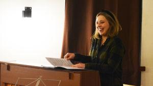 Ung kvinna sitter bakom piano och ler.