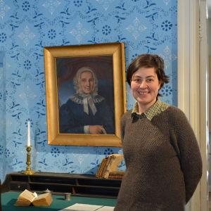 Museiintendent Ulrica Rosendahl vid ett porträtt av Virginia af Forselles