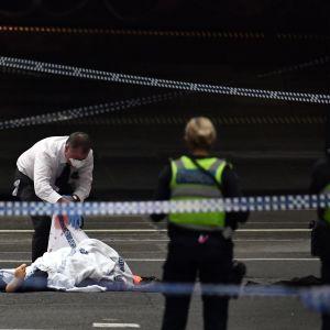 En polis inspekterar dödsoffret på attentatsplatsen i Melbourne på fredagen.