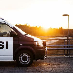 Kuvassa on poliisiauto, taustalla aurinko laskee.