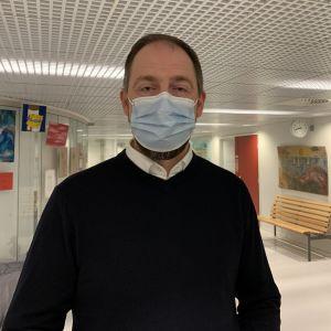 Mansperson står i skolkorridor, bär munskydd.